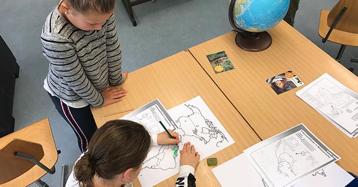Zwei Schülerinnen mit Weltkarte