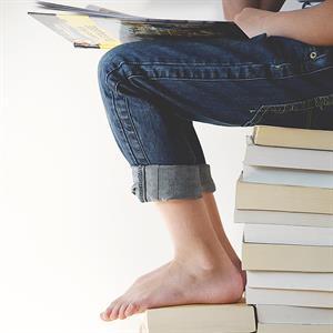 Ein Kind sitzt lesend auf einem Stapel Bücher