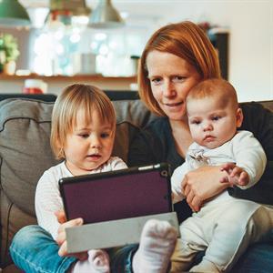 Eine Mutter schaut sich mit ihren Kindern etwas auf einem Tablet an